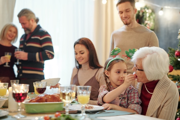 Adorable girl giving her great grandmother small tomato while both sitting by festive table with young and mature couples