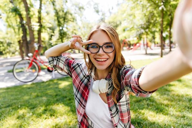 Adorable girl in glasses making selfie in park. outdoor shot of amazing blonde lady wears headphones in summer day.