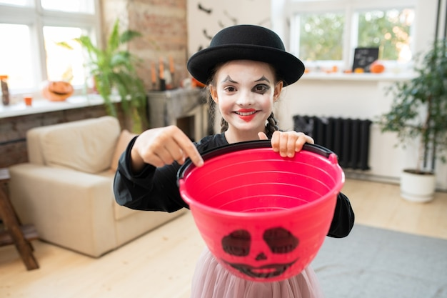 Adorable girl in halloween attire pointing at empty bucket for treats