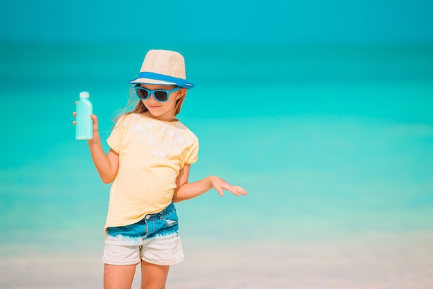 Adorable girl in hat with sun cream bottle on the beach at summer hot day. sun protection