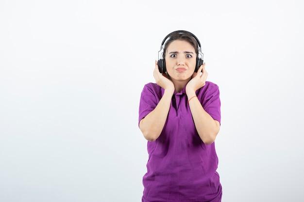 Adorabile ragazza in cuffia per ascoltare musica su bianco.