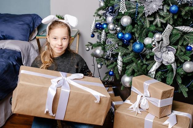 Adorable girl holding present box near xmas tree, free space. big christmas gift. christmas, holidays and childhood concept.