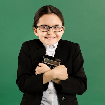 Adorable girl hugging calculator front view