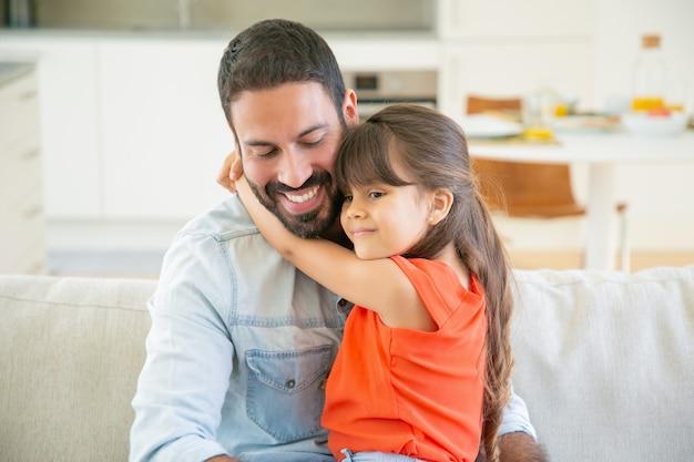 愛らしい少女が彼の膝の上に座っている間彼女のお父さんを抱き締めます。