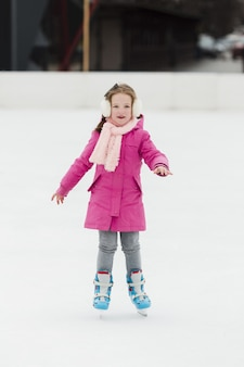 Adorable girl ice skating front view