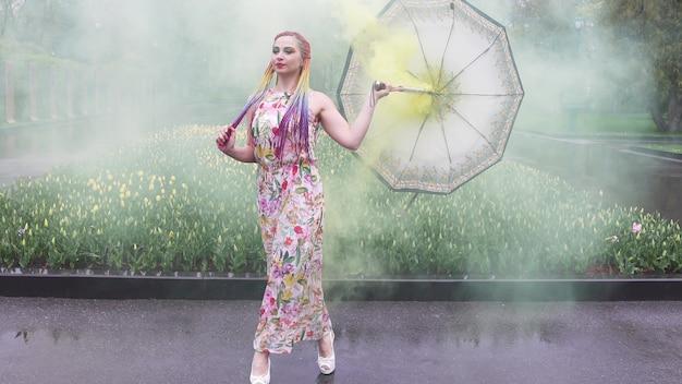 무지개 머리띠와 화장으로 꽃무늬 프린트가 있는 드레스를 입은 사랑스러운 소녀. 튤립이 있는 화단을 배경으로 노란 연기 속에 우산을 숨기고 춤을 춘다