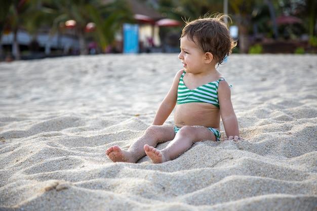Очаровательная девушка в купальнике сидит на песчаном пляже в лучах солнца.