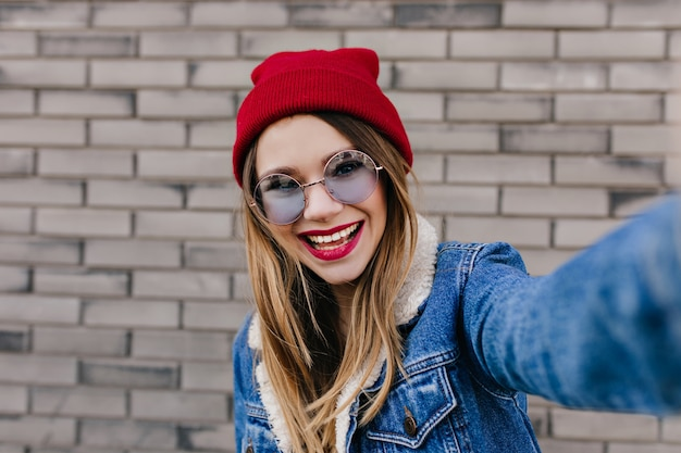 インスピレーションを得た表情で自分撮りを作る青いメガネの愛らしい女の子。レンガの壁に写真を撮る帽子の美しい若い女性の写真。