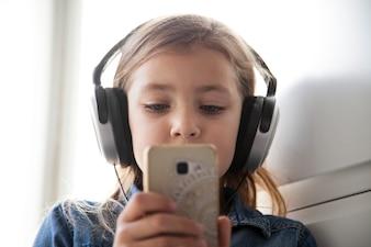 Adorable girl in headphones browsing smartphone