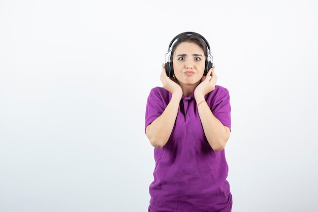 白で音楽を聴いているヘッドフォンの愛らしい女の子。