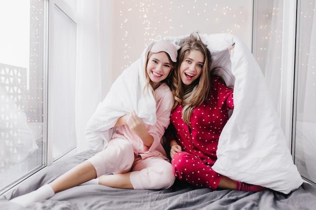 분홍색 잠옷과 양말 창 근처 어두운 시트에 앉아있는 귀여운 소녀. 담요와 함께 포즈를 취하고 웃고 빨간색 잠옷에 갈색 머리 여자를 흥분.