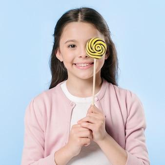 Adorable girl in studio holding lollipop