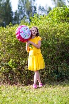 노란 드레스를 입은 사랑스러운 소녀가 꽃 모양의 축제 생일 다채로운 풍선을 들고 있습니다. 야외에서 행복한 아이