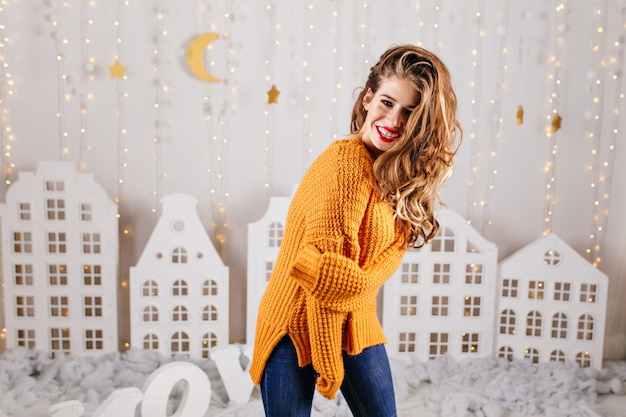 La ragazza adorabile è carina in posa in interni accoglienti. ritratto di donna riccia in maglione arancione