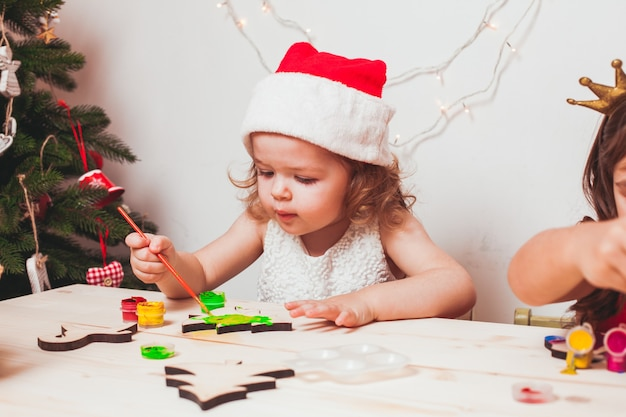 Очаровательная девушка рисует деревянные рождественские фигурки