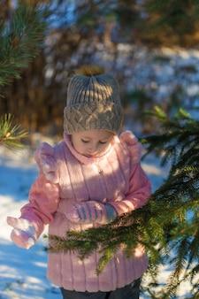 사랑스러운 소녀는 겨울 숲에서 소나무와 놀고있다. 행복한 어린 시절. kids outdoors. 겨울 재미있는 휴가 개념