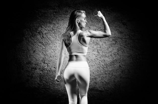Очаровательная девушка тренируется в тренажерном зале. она поднимает гантели вверх. вид сзади. понятие о бодибилдинге, фитнесе, здоровом образе жизни. световое пятно. смешанная техника