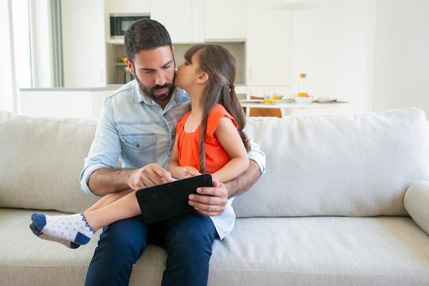 愛らしい少女が彼のタブレットを使用している間彼女のお父さんにキスします。