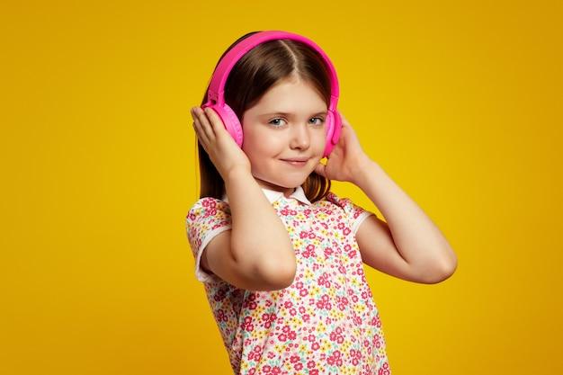Очаровательная девушка слушает музыку в белых наушниках, изолированных на желтой стене