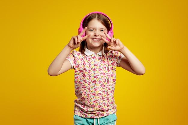 Очаровательная девушка слушает звуковую дорожку в розовых наушниках и делает жест мира