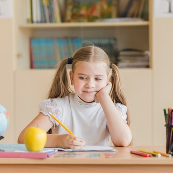 Adorable girl looking at apple during lesson