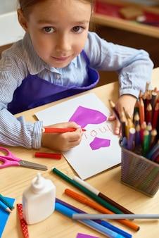 Adorable girl making handmade card for mom
