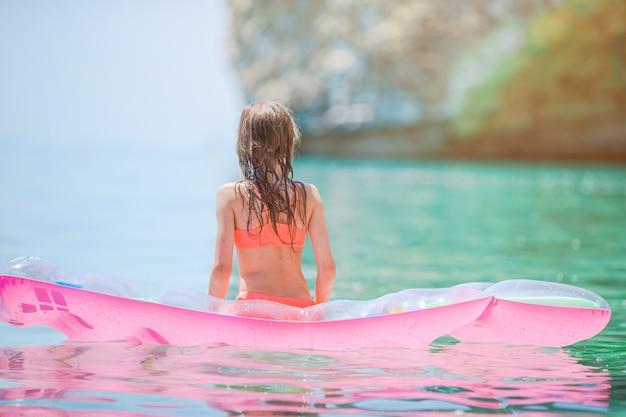 Очаровательная девушка на надувном надувном матрасе в море