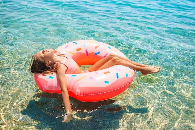 Очаровательная девушка на надувном матрасе в море