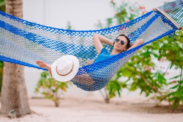 ハンモックでリラックスした熱帯の休暇に愛らしい少女