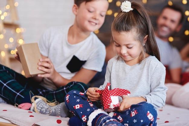 침대에서 크리스마스 선물을 열어 사랑스러운 소녀