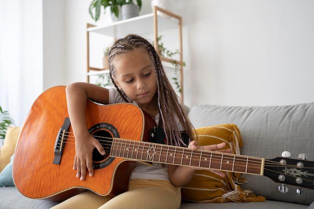 Adorabile ragazza che suona la chitarra a casa