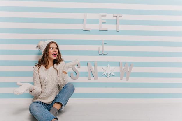 Очаровательная девушка радуется и восторженно позирует у стены в зимней одежде