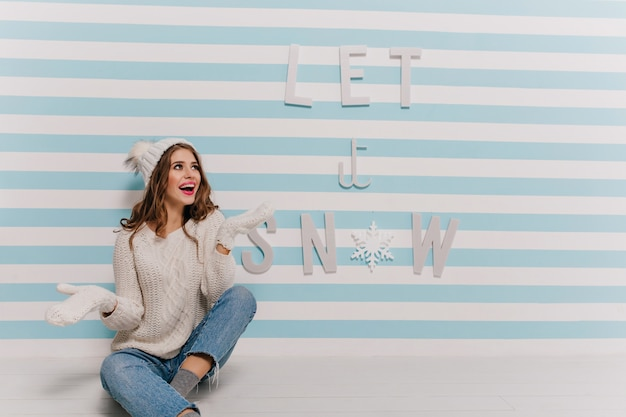Adorabile ragazza gioisce e posa con entusiasmo nel muro con abiti invernali