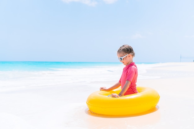 Adorable girl relaxing on inflatable air mattress on the beach