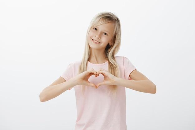 Очаровательная девушка показывает жест сердца и улыбается