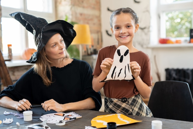 Adorable girl showing paper ghost and looking at camera