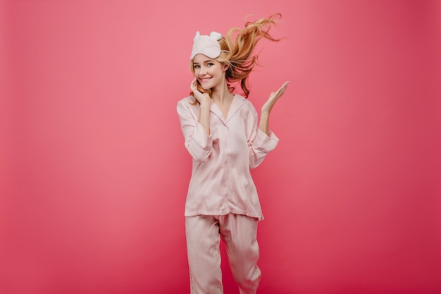 Adorable girl in silk night-suit dancing on pink wall. pretty woman with wavy hair spending morning