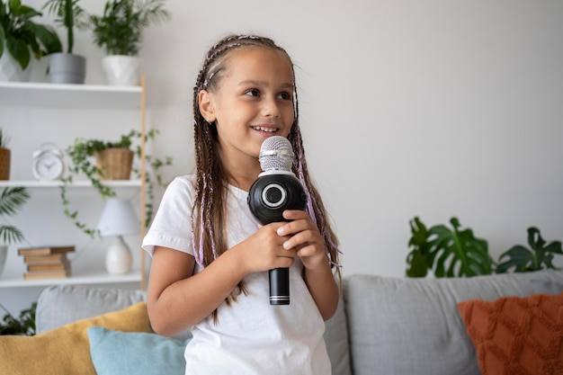 Adorable girl singing at a microphone at home