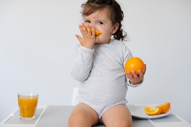 사랑스러운 소녀 앉아서 그녀의 오렌지를 즐기고