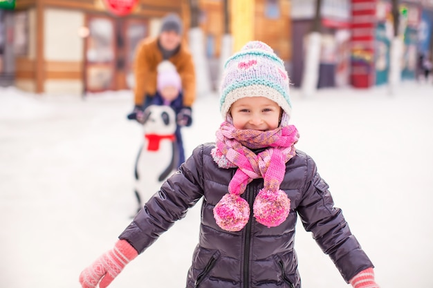 Adorable girl on skating rink, dad with little sister