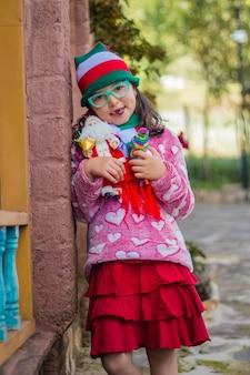 Adorabile ragazza sorridente e tenendo il suo giocattolo di babbo natale