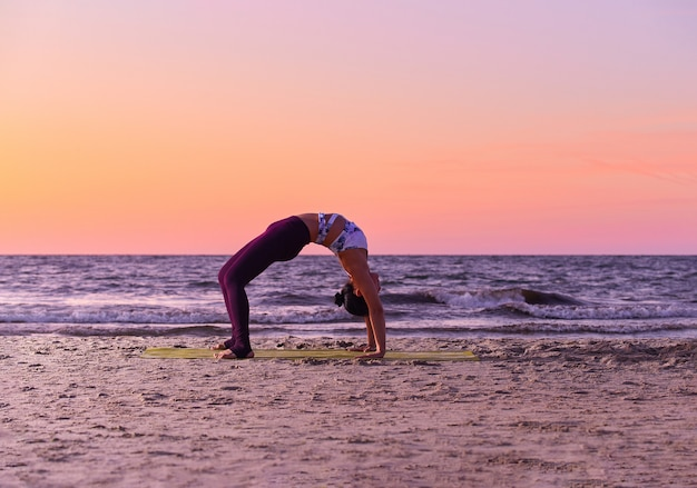 Adorable girl in sportswear is doing yoga by the sea, bends, standing in the trough.