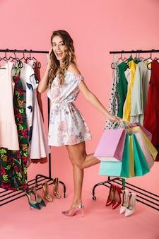 Очаровательная девушка стоит в магазине возле вешалки и держит разноцветные сумки, изолированные на розовом