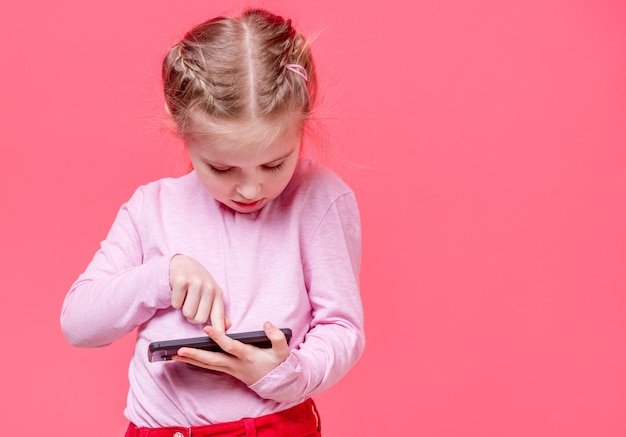 Adorable girl using smartphone over pink background