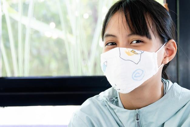 Очаровательная девушка в маске из хлопка закрывает рот и нос