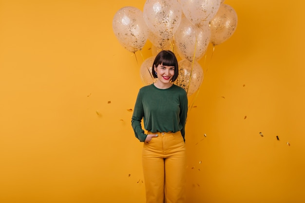 Adorabile ragazza con palloncini in posa con la mano in tasca. ritratto di bella donna castana sorridente alla festa.