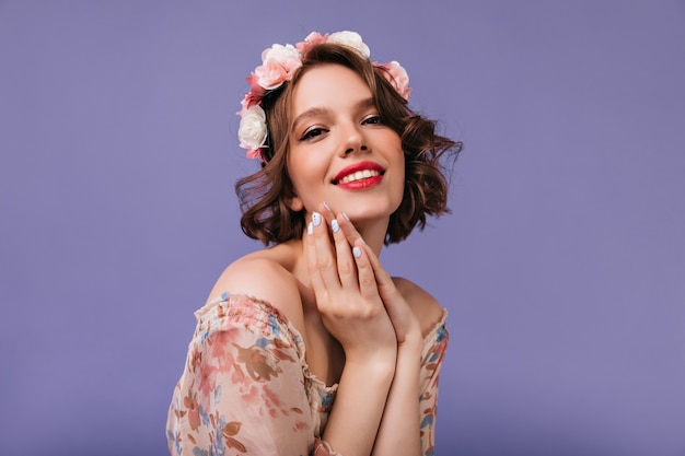 Adorable girl with beautiful flowers in hair posing. inspired white woman with sincere smile standing.