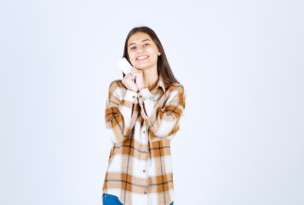白い壁に立っている空白の名刺を持つ愛らしい女の子。