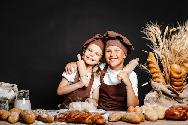 Adorable girl with brother cooking