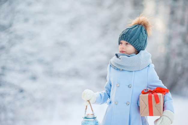 Adorable girl with christmas box gift in winter outdoors
